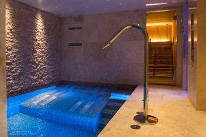 Luxury well-being pool with Crema Europa tiles and wall cladding