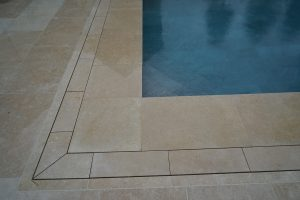 Pool terrace drainage in a contemporary stone - Fossil Pearl Satin Limestone.