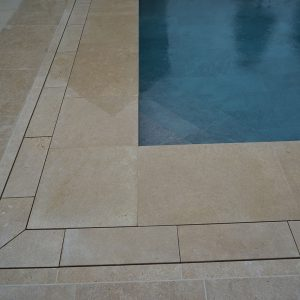 Pool terrace drainage in a contemporary stone - Fossil Pearl Satin Limestone.
