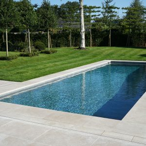 Fossil Pearl Satin Contemporary Limestone around a pool.