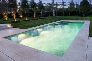 Fossil Pearl Satin Limestone pool coping with Overlip. Pool tilled with a 10mm thick grey porcelain.