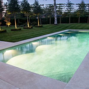 Fossil Pearl Satin Limestone pool coping with Overlip. Pool tilled with a 10mm thick grey porcelian.