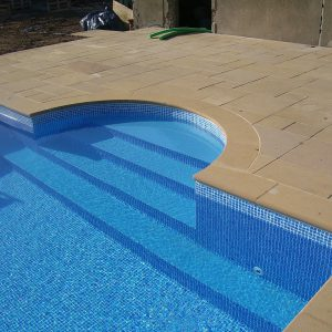 Swimming pool copings in Timsbury Sandstone with Roman End and matching paving.