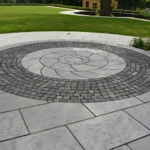Bespoke cut Farley Black circle kit set within granite setts.