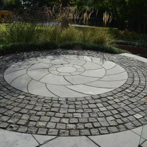 Granite setts around a bespoke cut circle kit in Farley Black Limestone.