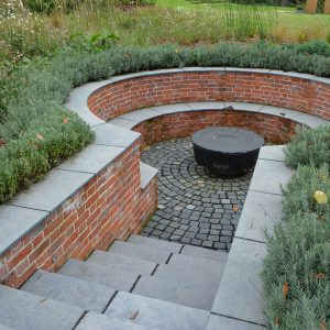 Farley Black Limestone bespoke steps and radius seat, with granite setts.