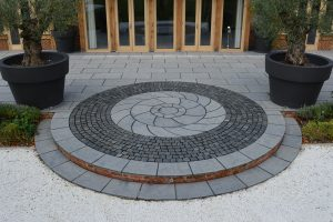 Bespoke cut Farley Black circle kit set within granite setts.
