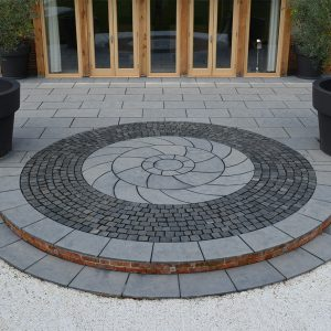 Farley Black step to lawn with bespoke circle kit and Granite setts.