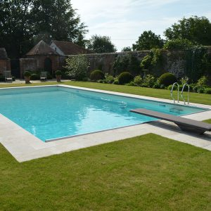 Travertine pool copings on a walled garden pool.