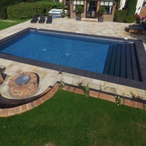 Boston Porcelain pool coping and steps, with Cotswold Mint Riven Sandstone surrounds.