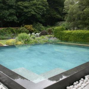 Chattis Black Basalt pool coping, double bullnose on an infinity edge.